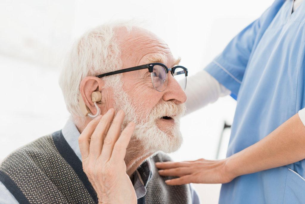 elderly man getting a hearing aid